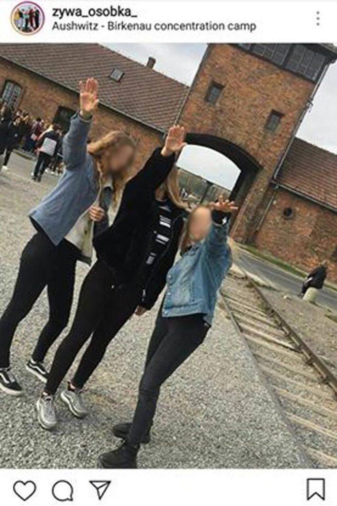 """Trzy młode dziewczyny opublikowały zdjęcie, na którym wykonują nazistowski gest """"sieg heil"""" przed bramą byłego obozu koncentracyjnego Birkenau."""
