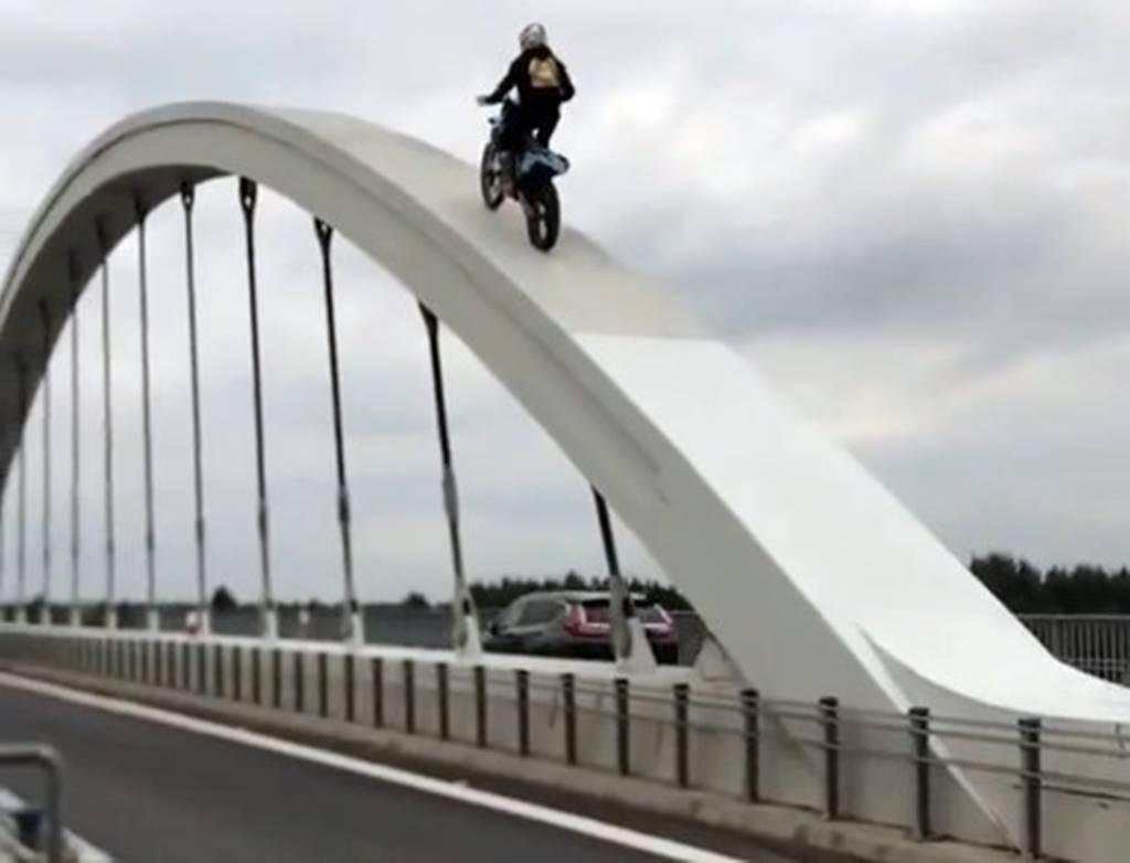 Motocyklem crossowym wjechał na łukowe przęsło mostu. Zrobił to dla pieniędzy.W tym czasie na moście odbywał się normalny ruch drogowy.